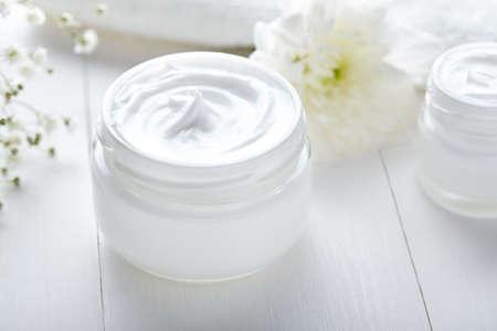 Anti rimpel cosmetische crème met kruiden bloemen gezicht, huid en lichaamsverzorging hygiëne vocht lotion wellness therapie masker in glazen pot met handdoek op witte achtergrond