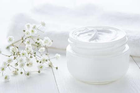 흰색 배경에 수건으로 유리 항아리에 요구르트 크림 아름다움 화장품 제품 웰빙 및 이완 화장 마스크
