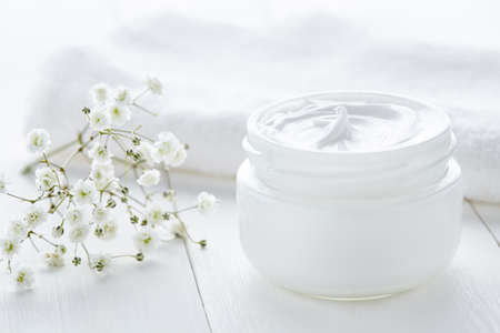 Yogurt cream beauty cosmetic product wellness and relaxation makeup mask in glass jar with towel on white background