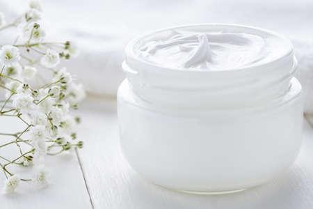 Dermatologia crema cosmetica con i fiori prodotto skincare igienico in vaso di vetro su sfondo bianco Archivio Fotografico - 57242914