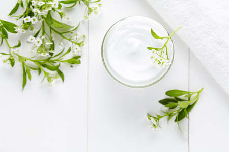 白い背景の上のガラスの瓶に花スキンケア製品と天然ハーブ温泉化粧品衛生クリーム