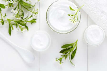 Medische behandeling cosmetische crème met kruiden bloemen hygiënische huidverzorgingsproduct wellness en ontspanning masker in glazen pot op een witte achtergrond Stockfoto - 57242852