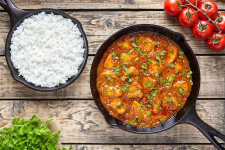 Indisches Lebensmittel des traditionellen würzigen Fleisches des Tikka-masala Huhns mit Reistomaten und -petersilie in der Roheisenbratpfanne auf hölzernem Hintergrund der Weinlese
