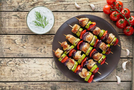 Turkey or chicken meat shish kebab skewers with tzatziki sauce, garlic and tomatoes on rustic wooden table background. Traditional barbecue grill food