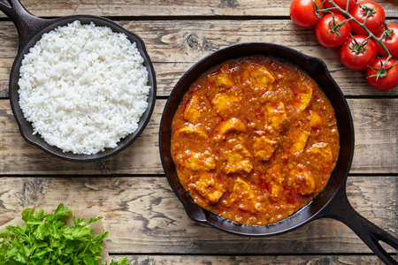 pan asian: Chicken tikka masala traditional Asian spicy meat food with rice tomatoes and parsley in cast iron pan on vintage wooden background