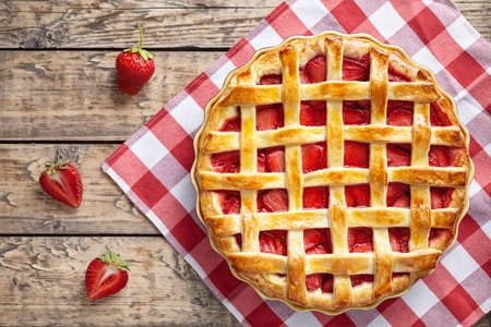 Summer traditional strawberry pie tart cake sweet baked pastry food on rustic wooden table background