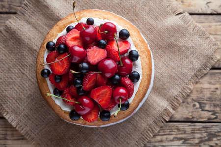 Fresco torta di fragole prime dolci fatti in casa dessert forno tradizionale gourmet estivo decorato con frutti di bosco e panna montata sul tavolo fondo rustico Archivio Fotografico - 60966674