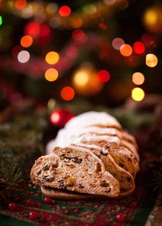 Traditioneller Dresdner deutscher Weihnachtskuchen Stollen mit Marzipan, Beeren-Nüssen, Zimt, anhebend auf einer rustikalen hölzernen festlichen Tabelle. Feiertagsweihnachtsfeier, gemütliche, romantische Dekorationen.