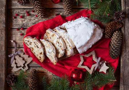 atmospheric: Traditional German Dresdner Christmas cake Stollen with Berries Nuts and Raising on a rustic wooden festive table. Holiday xmas celebration baking fruitcake. Atmospheric, cozy, romantic decorations.