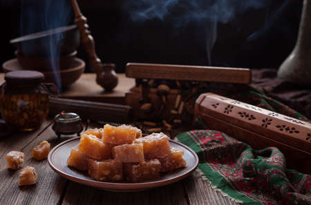atmospheric: Arabic traditional gourmet dessert rahat lukum, lokum powdered with sugar, eastern candy. Turkish Still life. Holidays ramadan, seker bayram concept. Smoky hookah atmospheric. Stock Photo