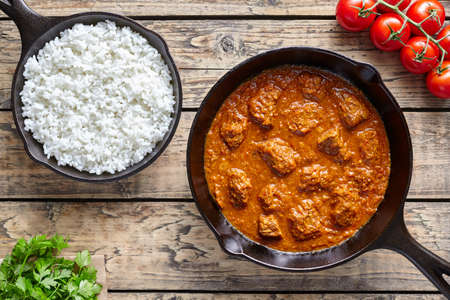 Madras: Traditional Beef Madras Indian spicy lamb food with rice in cast iron pan on vintage wooden table background. Delicious India culture restaurant dish. Stock Photo