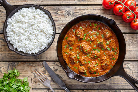Beef Madras curry slow cook Indian spicy chili lamb food with rice in cast iron pan on vintage wooden table background. Traditional India culture restaurant dish.