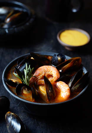 Traditional Marseille Bouillabaisse fish soup with prawns, mussels tomato, squid. Sauce Rouille. Prepare in France and Spain. Black background.