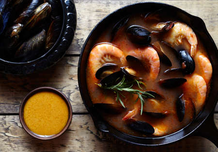 Bouillabaisse fish soup with prawns, mussels tomato, lobster. Sauce Rouille. Traditional France dish. Rustic style background. Flat lay.