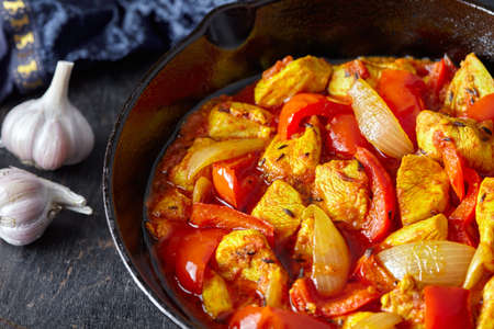 dietetic: Chicken jalfrezi Indian culture fried spicy curry chilli sauce meat and vegetables healthy dietetic food dish in cast iron pan on vintage wooden table background. Stock Photo