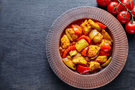 dietetic: Chicken jalfrezi Indian traditional fried spicy curry chilli meat and vegetables healthy dietetic food in clay dish on vintage table background. Stock Photo