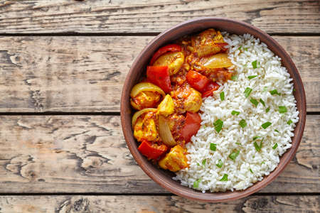 dietetic: Chicken jalfrezi Indian spicy curry chilli meat with basmati rice and vegetables healthy dietetic asian food in clay dish on vintage table background.