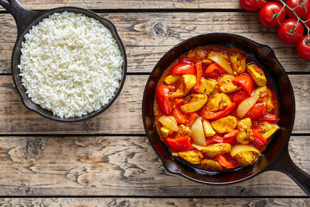 Chicken jalfrezi dietetic traditional Indian curry spicy fried meat with vegetables and basmati rice food in cast iron pan on vintage table background Stock Photo