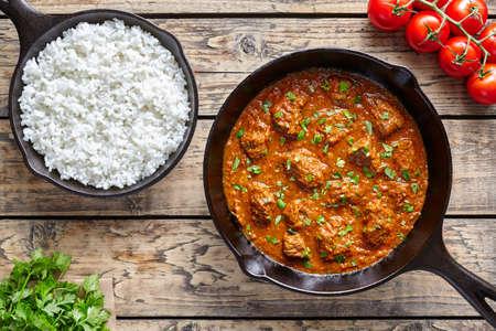 쇠고기 마드라스 카레 천천히 쿡 빈티지 나무 테이블 배경에 주철 팬에서 인도 매운 garam masala 양고기 음식. 전통적인 인도 문화 레스토랑 요리입니다.