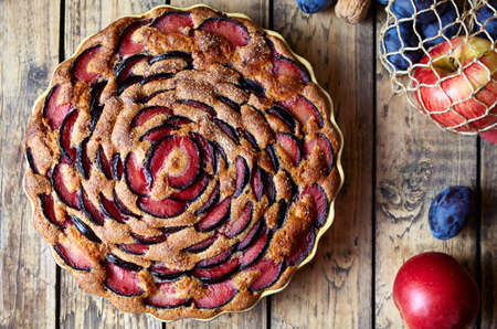 speciality: Wholegrain plum pie zwetschgendatschi on the ceramic plate and wooden table. Rustic style. Top viev.