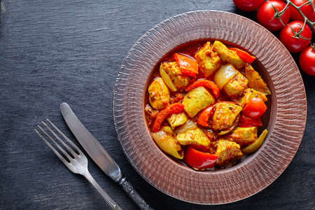 dietetic: Chicken jalfrezi Indian restaurant fried spicy curry chilli meat and vegetables healthy dietetic asian food in clay dish on vintage table background. Stock Photo