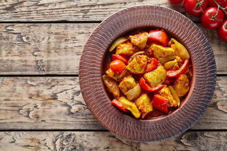 dietetic: Chicken jalfrezi Indian spicy curry chilli meat and vegetables healthy dietetic asian food in clay dish on vintage table background.