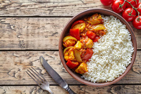 dietetic: Chicken jalfrezi traditional homemade Indian spicy curry chilli meat with rice and vegetables healthy dietetic asian food in clay dish on vintage table background.