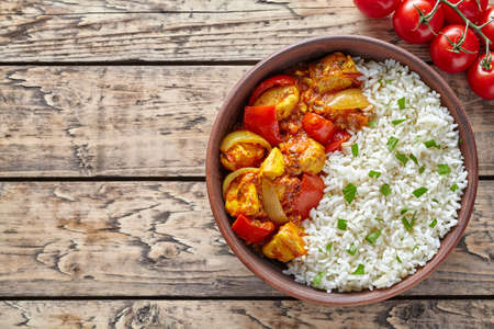 dietetic: Chicken jalfrezi traditional Indian spicy curry chilli meat with basmati rice and vegetables healthy dietetic asian food in clay dish on vintage table background.
