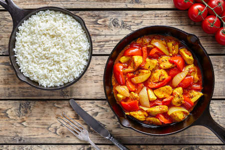 dietetic: Chicken jalfrezi dietetic traditional Indian curry spicy fried meat with vegetables and basmati rice asian food in cast iron pan on vintage table background
