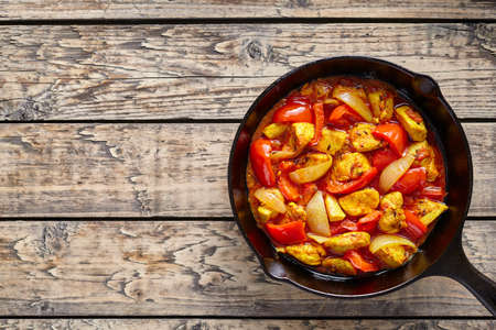 dietetic: Chicken jalfrezi dietetic traditional Indian culture curry spicy fried meat with vegetables asian food in cast iron pan on vintage table background