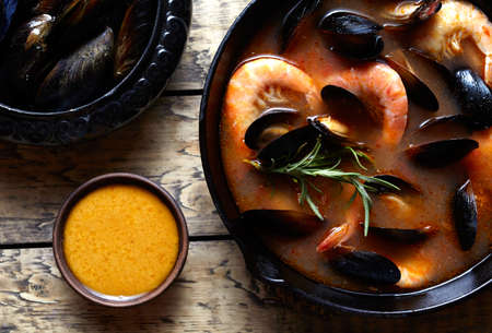Bouillabaisse fish soup with seafood, prawns, mussels tomato, lobster. Sauce Rouille. Traditional Marseille France dish. Rustic style background. Flat lay. Stock Photo
