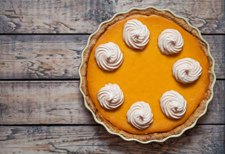 Festive Homemade Delicious Pumpkin pie with whipped cream and spices made for Thanksgiving and halloween, top view. Stock Photo