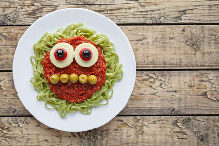 fake smile: Green spaghetti pasta creative spooky halloween food monster with smile, fake blood tomato sauce and funny big mozzarella eyeballs holiday decoration kid party meal on vintage wooden table background.