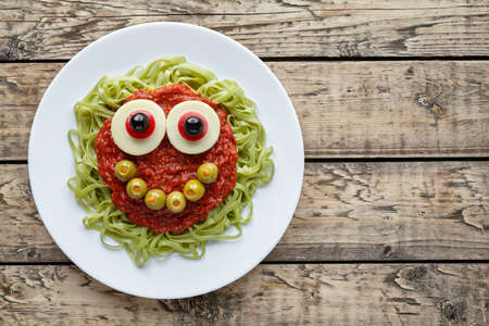 fake smile: Green spaghetti pasta creative halloween food monster with cute smile, fake blood tomato sauce and big mozzarella eyeballs holiday decoration kid party meal on vintage wooden table background.