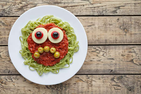 fake smile: Green spaghetti pasta creative spooky halloween food monster with sad smile, fake blood tomato sauce and big mozzarella eyeballs holiday decoration kid party meal on vintage wooden table background.