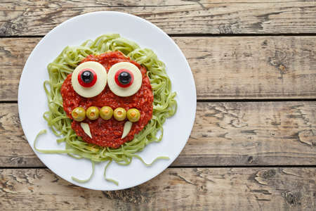 fake smile: Green spaghetti pasta creative spooky halloween vegetarian food vampire monster with smile, fake blood tomato sauce and funny big mozzarella eyeballs holiday decoration kid party meal on vintage table