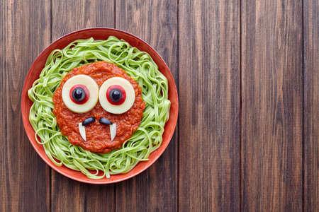 fake smile: Green spaghetti pasta spooky halloween vegetarian food vampire monster with smile, fake blood tomato sauce and funny big mozzarella eyeballs decoration kid party meal on vintage table Stock Photo