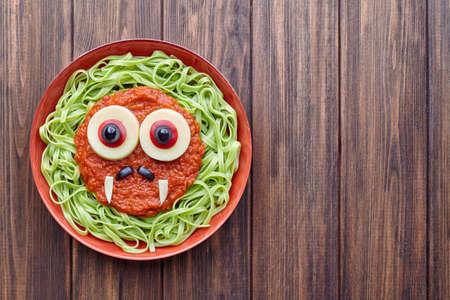fake smile: Green spaghetti pasta scary halloween food vampire monster with smile, fake blood tomato sauce moustaches and funny big mozzarella eyeballs decoration kid party meal on vintage table Stock Photo