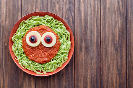 terrifying: Green spaghetti creative pasta scary halloween food vampire monster with fake blood tomato sauce and funny big mozzarella eyeballs decoration kid party meal on vintage table. Stock Photo