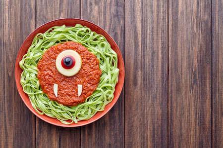 Verde spaghetti creativo halloween pasto Ciclopi alimentari mostro con falsi salsa di pomodoro e mozzarella di sangue bulbo oculare decorazione celebrazione pasto ragazzo partito sul tavolo d'epoca. Archivio Fotografico - 66276157