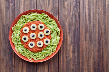 terrifying: Green spaghetti creative pasta scary halloween party food monster meal with fake blood tomato sauce and many mozzarella eyeballs terrifying decoration celebration kid party meal on vintage table.