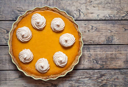 Traditional Homemade Delicious Pumpkin pie with whipped cream and spices made for Thanksgiving, Halloween, top view.