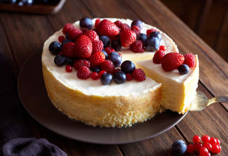 Close up. Creamy mascarpone cheese cake with strawberry and winter berries. New York Cheesecake. Close up. Christmas dessert. Healthy food. Creative atmospheric decoration.
