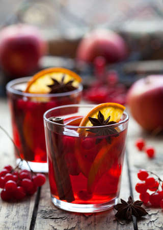 Winter warm drink. Christmas mulled red wine or sangria with cinnamon sticks, anise stars, oranges and berries in a pot on a rustic wooden table