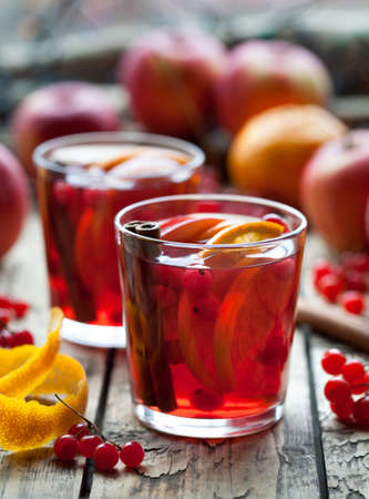 Sangria in glasses with ingredients - orange and apple slices, berries, cinnamon sticks in a wooden rustic table. Creative decoration.