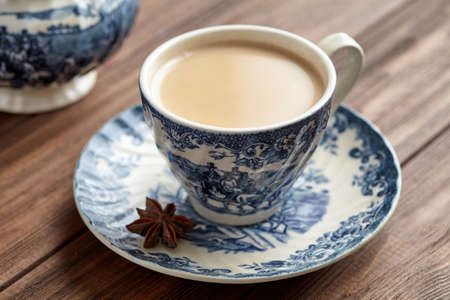Masala tea chai latte homemade traditional Indian milk with spices beverage in porcelain cup on wooden table background