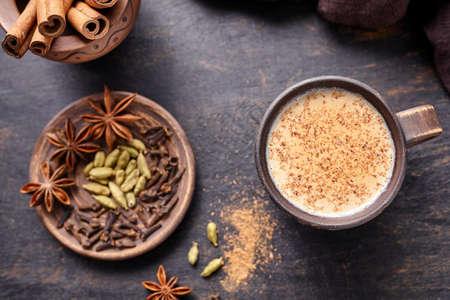Masala thee chai latte traditionele warme Indische melk zoete gekruide drank, nootmuskaat, gember, cinammon sticks, verse kruiden mengen, kardemom, anijs organische infusie gezonde wellness drank in rustieke klei kop