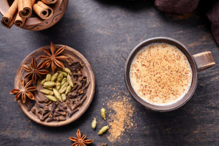 Masala tea chai latte traditional hot Indian sweet milk spiced drink, nutmeg, ginger, cinammon sticks, fresh spices blend, cardamom, anise organic infusion healthy wellness beverage in rustic clay cup Archivio Fotografico