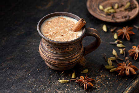 Masala pulled tea chai latte hot Indian sweet milk spiced drink, ginger, fresh spices and herbs blend, anise organic infusion healthy wellness beverage teatime ceremony in rustic clay cup Archivio Fotografico