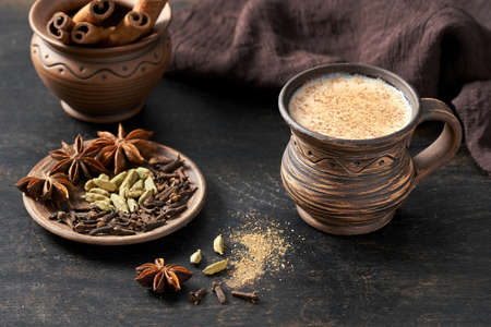 Masala pulled tea chai latte hot Indian sweet milk spiced drink, cinnamon stick, cloves, fresh spices and herbs blend, organic infusion healthy wellness beverage teatime ceremony in rustic clay cup